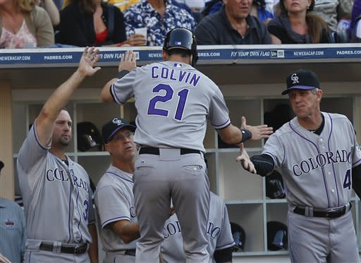Colorado Rockies' Tyler Colvin (21) is congratulated at the dugout after scoring on a Ramon Hernandez base hit against the San Diego Padres during the fourth inning of a baseball game on Saturday, July 21, 2012, in San Diego. (AP Photo/Lenny Ignelzi)