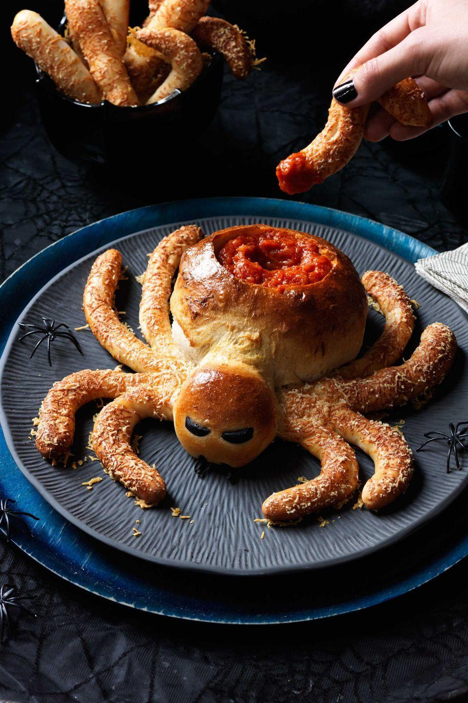 """<p>Spin a web of doughy deliciousness with this party-perfect Halloween appetizer. If you can't find pizza dough at your supermarket, try a local pizza parlor, which will likely sell you a fresh ball. For extra effect, sprinkle the legs with poppy seeds, in addition to Parmesan.<br></p><p><a href=""""https://www.womansday.com/food-recipes/food-drinks/recipes/a11906/saucy-spider-hairy-leg-sticks-recipe-123433/"""" rel=""""nofollow noopener"""" target=""""_blank"""" data-ylk=""""slk:Get the Saucy Spider recipe."""" class=""""link rapid-noclick-resp""""><em>Get the Saucy Spider recipe.</em></a></p>"""