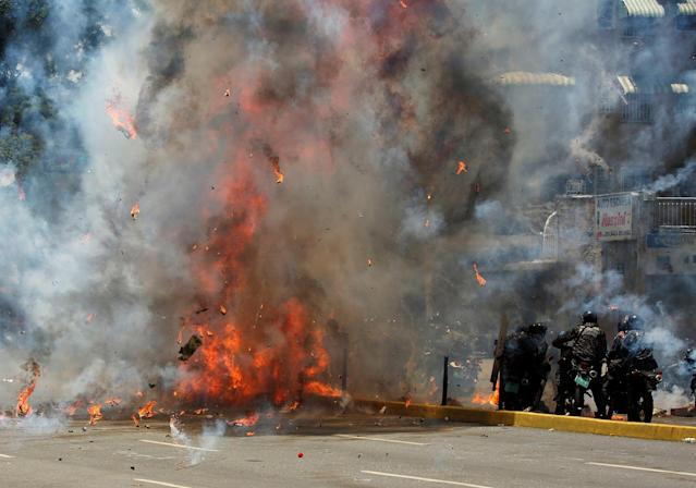 <p>Flames erupt as clashes break out near security forces members (R) while the Constituent Assembly election is being carried out in Caracas, Venezuela, July 30, 2017. (Carlos Garcia Rawlins/Reuters) </p>