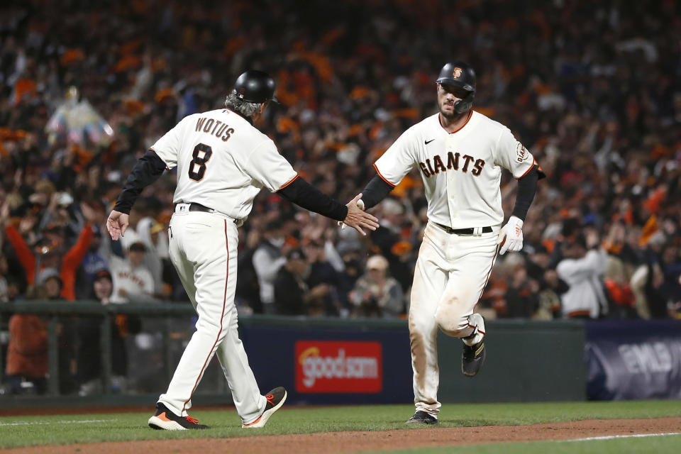 San Francisco Giants' Kris Bryant, right, is congratulated by San Francisco Giants third base coach Ron Wotus (8) after hitting a home run against the Los Angeles Dodgers during the seventh inning of Game 1 of a baseball National League Division Series Friday, Oct. 8, 2021, in San Francisco. (AP Photo/Jed Jacobsohn)