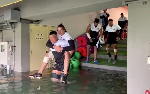 Japan's national rugby team waded through floodwater to reach the pitch for practice, with a decision still to be made on Sunday's matches - Credit: Japan Rugby Football Union/Reuters