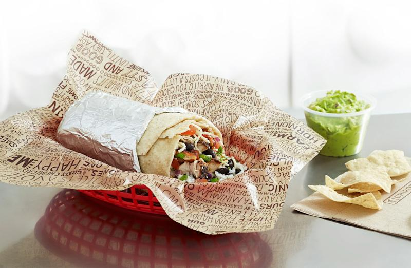 A Chipotle burrito in a plastic basket next to an order of chips and a cup of guacamole.