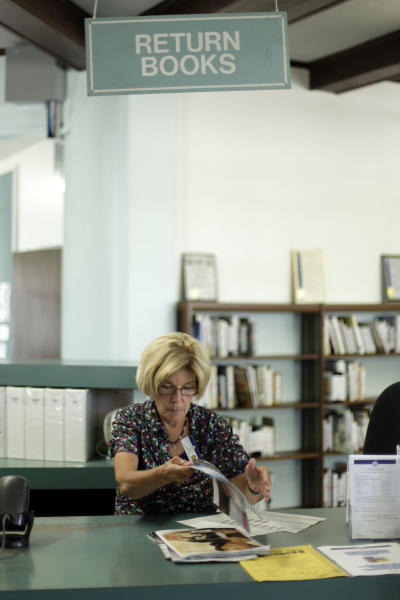Library clerk Jane Stahl organizes items at a San Diego Public Library Friday, June 8, 2012, in San Diego. Stahl has worked for the city as a librarian for seven years. Voters in San Diego and San Jose overwhelmingly approved ballot measures last week to roll back municipal retirement benefits - and not just for future hires but for current employees. (AP Photo/Gregory Bull)