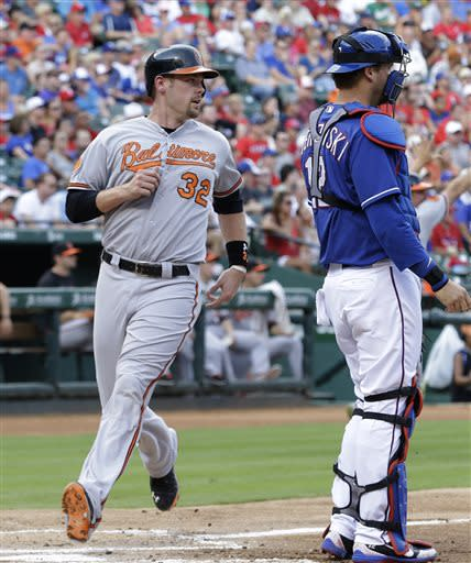 Baltimore Orioles Matt Wieters (32) scores on a single by Brian Roberts with Texas Rangers catcher A.J. Pierzynski (12) standing by during the second inning of a baseball game Sunday, July 21, 2013, in Arlington, Texas. (AP Photo/LM Otero)