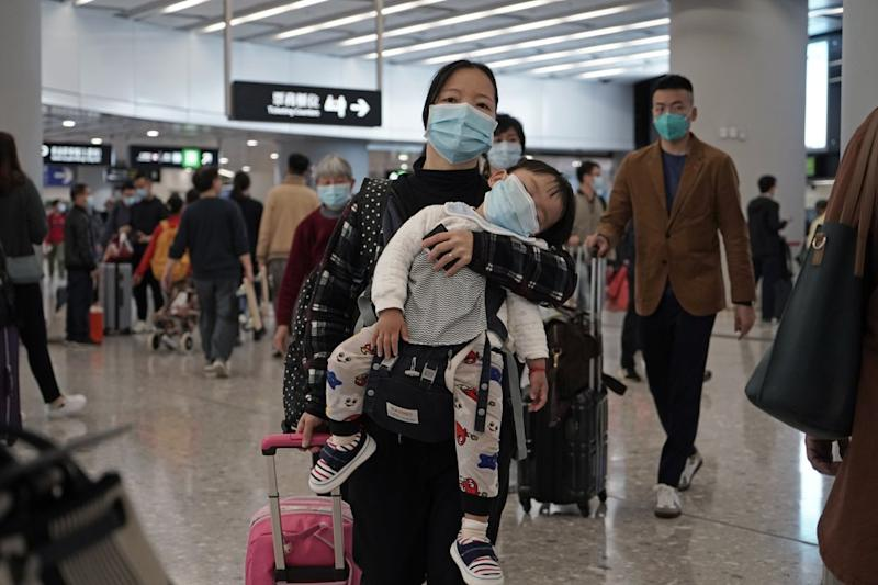 A mother with her child at a train station in Hong Kong, both wearing protective face masks.