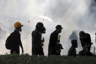 FILE - In this Sunday, Nov. 17, 2019, file photo, pro-democracy protestors react as police fire tear gas at Hong Kong Polytechnic University in Hong Kong. By day, the small commercial kitchen in a Hong Kong industrial building produces snacks. At night, it turns into a secret laboratory assembling a detox kit to help frontline pro-democracy protesters counter ill-effects from repeated exposure to tear gas. (AP Photo/Kin Cheung, File)