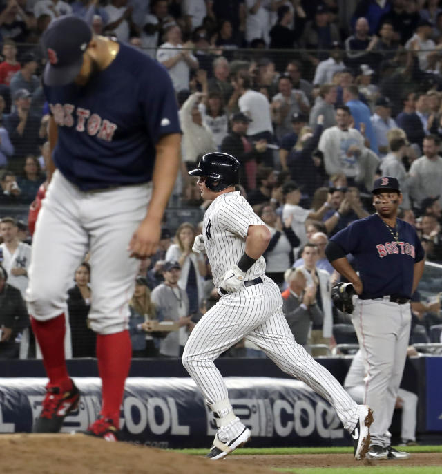 New York Yankees' Luke Voit, center, rounds the bases after hitting a two-run home run off Boston Red Sox starting pitcher Eduardo Rodriguez, left, during the second inning of a baseball game Thursday, Sept. 20, 2018, in New York. Red Sox third baseman Rafael Devers is at right. (AP Photo/Julio Cortez)