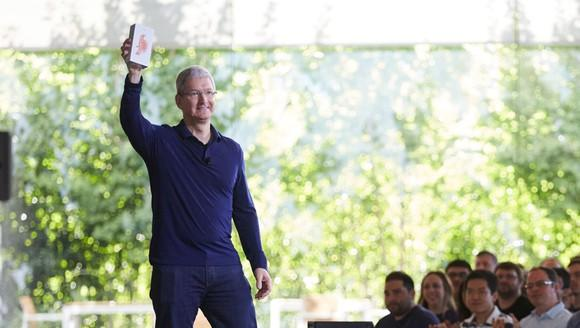 Tim Cook holding an iPhone in front of Apple employees