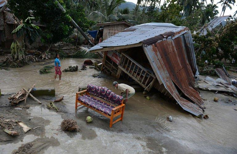 Residents clean up next to their damaged house in New Bataan town on December 5, 2012, a day after Typhoon Bopha hit the province. The Philippine government said typhoon gusts of up to 210 kilometres (130 miles) an hour had destroyed thousands of homes and other buildings, leaving residents with little more than the clothes on their backs