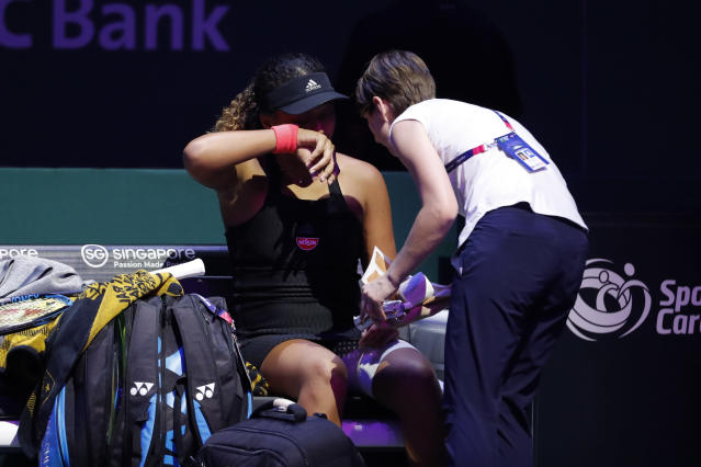Naomi Osaka of Japan been check before retiring with an injury while competing against Kiki Bertens of the Netherlands during their women's singles match at the WTA tennis finals in Singapore, Friday, Oct. 26, 2018. (AP Photo/Vincent Thian)