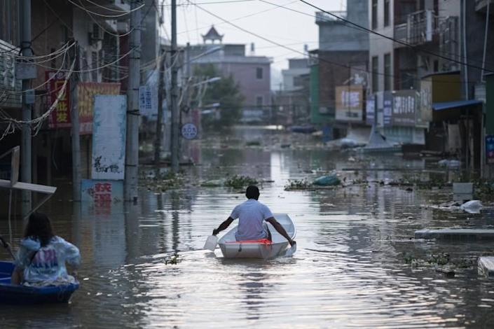 A man paddles a boat through the flooded main street of Dixi village. Poyang, Jiangxi province, China on July 14