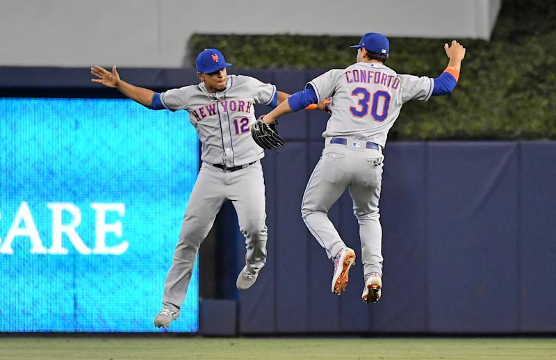 Jul 14, 2019; Miami, FL, USA; New York Mets center fielder Juan Lagares (12) and New York Mets right fielder Michael Conforto (30) celebrate after defeating the Miami Marlins at Marlins Park. Mandatory Credit: Jasen Vinlove-USA TODAY Sports