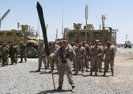 U.S. Marines stand at attention during a transfer of authority ceremony at Shorab camp, in Helmand province, Afghanistan