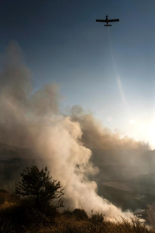 A firefighting aircaft douses the flames in an effort to contain a fire near the Kotsiatis area, on the outskirts of Cyprus' capital Nicosia on July 4, 2021