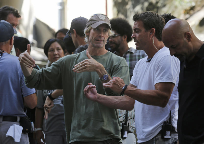 "American film director Michael Bay, center, talks with his film crew during the filming of a scene for their latest movie ""Transformers 4: Age of Extinction"" in Hong Kong Friday, Oct. 18, 2013. Bay was attacked on Thursday and slightly injured on the set of the fourth installment of the ""Transformers"" movie series filming in Hong Kong, police said. The spokeswoman said Bay suffered a minor injury to his face but declined medical treatment. (AP Photo/Kin Cheung)"