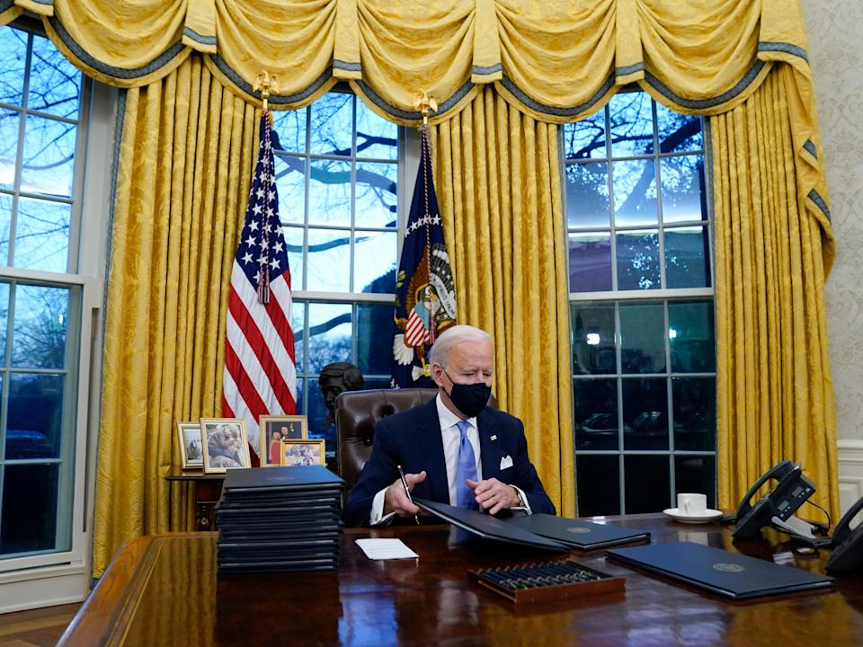 President Joe Biden signs his first executive orders in the Oval Office of the White House on Wednesday, Jan. 20, 2021