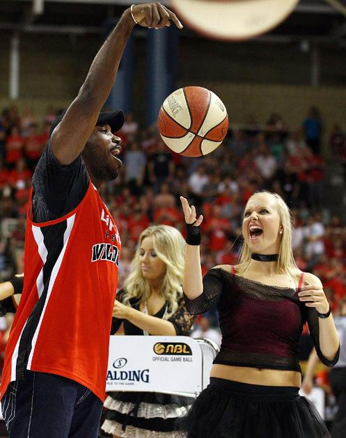 PERTH, AUSTRALIA - JANUARY 21:  West Indian cricketer Chris Gayle celebrates after shooting balls at a time-out during the round 15 NBL match between the Perth Wildcats and the Townsville Crocodiles at Challenge Stadium on January 21, 2011 in Perth, Australia.  (Photo by Paul Kane/Getty Images) *** Local Caption *** Chris Gayle