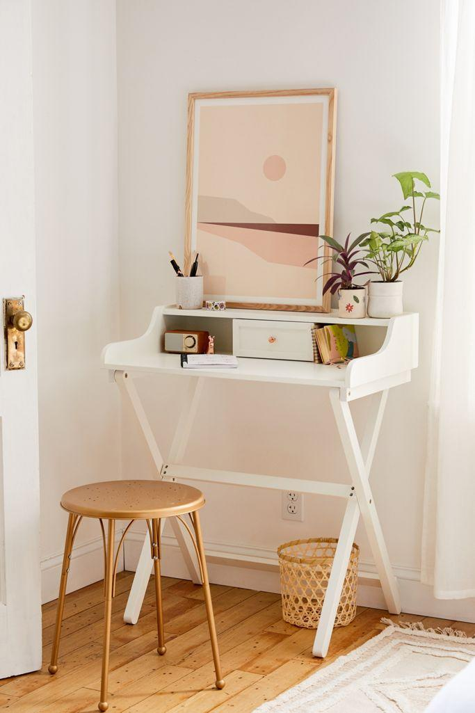 """<h3>Urban Outfitters Cory Folding Desk</h3><br>This chic-compact desk style boasts a hidden fold-up punch — meaning you can tuck this bad boy out of sight and away when you're not using it to be a WFH boss.<br><br><strong>Urban Outfitters</strong> Cory Folding Desk, $, available at <a href=""""https://go.skimresources.com/?id=30283X879131&url=https%3A%2F%2Fwww.urbanoutfitters.com%2Fshop%2Fcory-folding-desk"""" rel=""""nofollow noopener"""" target=""""_blank"""" data-ylk=""""slk:Urban Outfitters"""" class=""""link rapid-noclick-resp"""">Urban Outfitters</a>"""