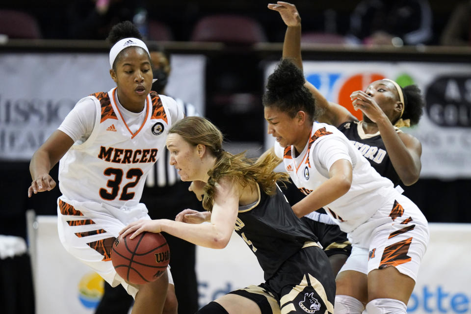 Wofford guard Helen Matthews (5) drives the ball between Mercer forward Jaron Dougherty (32) and Mercer guard Jill Harris (0) in the first half of an NCAA women's college basketball championship game for the Southern Conference tournament, Sunday, March 7, 2021, in Asheville, N.C. (AP Photo/Kathy Kmonicek)