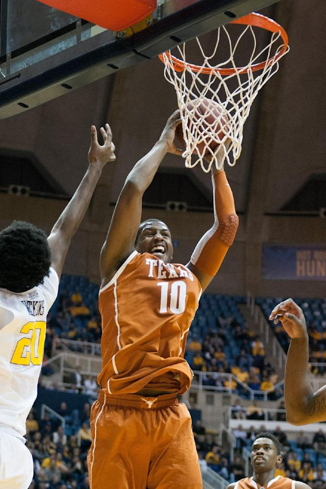 Texas' Jonathan Holmes, center, brings down a rebound during the second half of an NCAA college basketball game against West Virginia, Monday, Jan. 13, 2014, in Morgantown, W.Va. Texas won 80-69. (AP Photo/Andrew Ferguson)