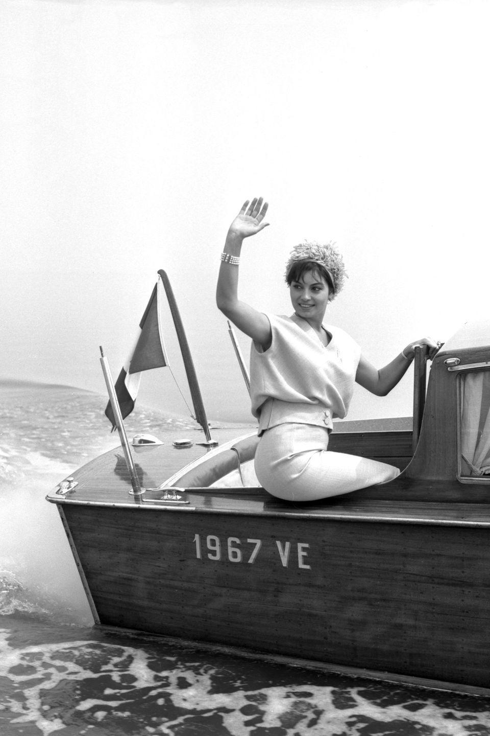 <p>Italian film star Rosanna Schiaffino waves to her fans as she arrives at an event in 1960 via water taxi. The actress sits on the stern of the vessel in a cream two-piece set and floral fascinator. </p>