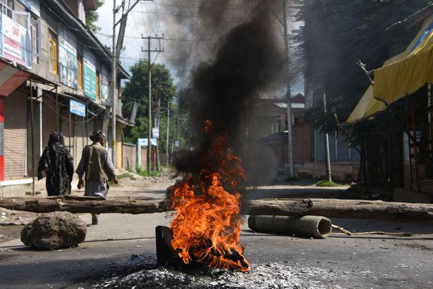 People walk past burning tires near a barricade during a protest against the abolishing of Article 370, on Aug. 20, 2019 in Srinagar, India.