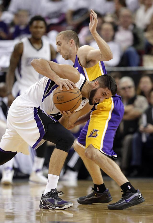 Sacramento Kings guard Greivis Vasquez, left, of Venezuela, ducks under the arm of Los Angeles Lakers guard Steve Blake as he drives during the first quarter of an NBA basketball game in Sacramento, Calif., Friday, Dec. 6, 2013. (AP Photo/Rich Pedroncelli)