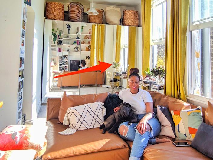 This image shows a woman and her dog sitting on a couch with mirrors in the background and windows on the right.