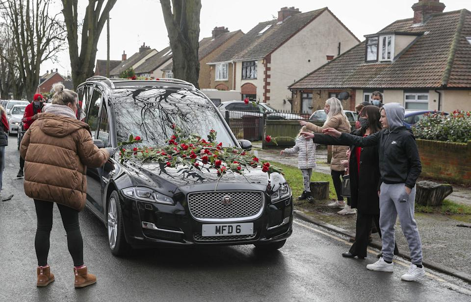 Members of the public place red roses on the hearse of Olly Stephens (PA) (PA Wire)