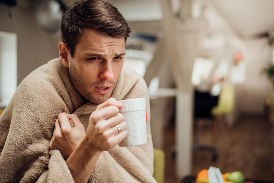 Young man shivering under the blanket and drinking tea