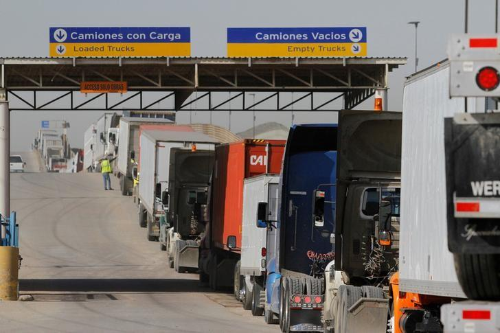 FILE PHOTO - Trucks wait in a long queue for border customs control to cross into the U.S. at the Otay border crossing in Tijuana