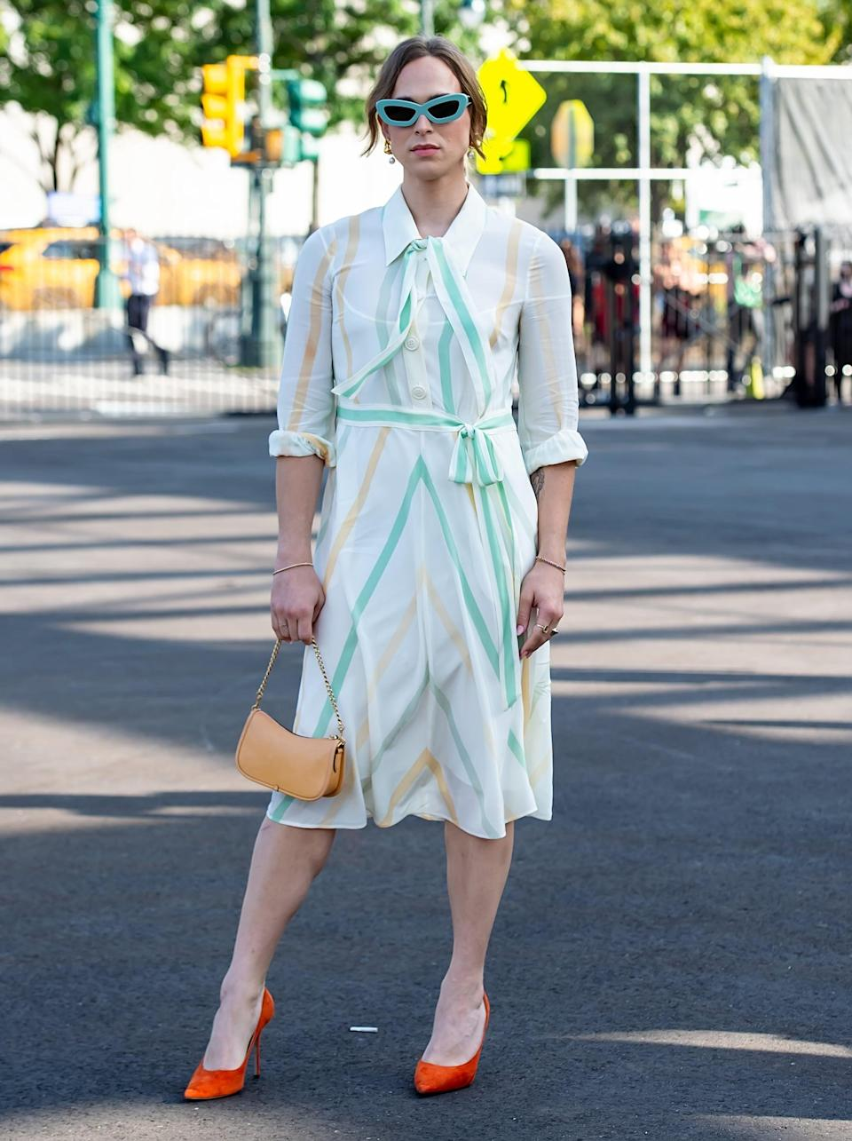<p>She styled a striped dress with bright orange heels, a tan handbag, and turquoise sunglasses.</p>