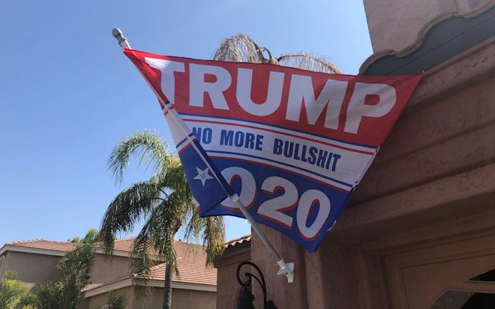 """A red and white flag reading """"TRUMP 2020: No More Bullshit"""" flutters in the breeze on a pole in front of a tan-coloured garage, with palm trees in the background - Laurence Dodds/Telegraph"""