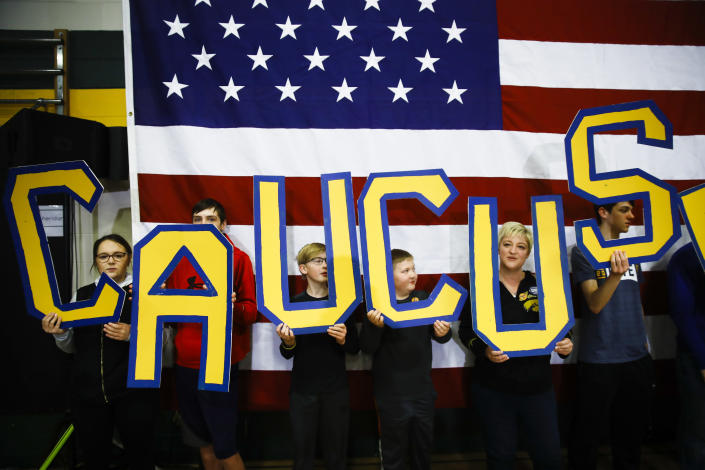 """Attendees hold letters that read """"CAUCUS"""" during a campaign event for Democratic presidential candidate former South Bend, Ind., Mayor Pete Buttigieg at Northwest Junior High, Sunday, Feb. 2, 2020, in Coralville, Iowa. (AP Photo/Matt Rourke)"""