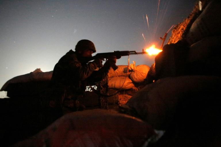 A Ukrainian serviceman fires at Russia-backed separatists during night combat on the front line near Novolugansk in the Donetsk region on November 14, 2019
