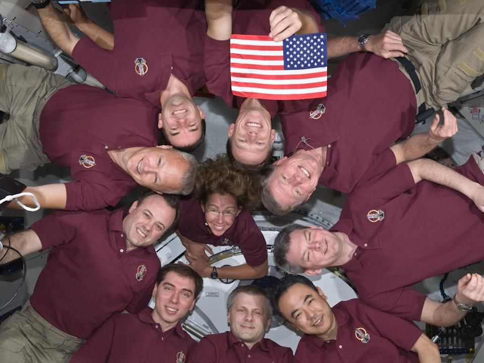 The crews of STS-135 and Expedition 28 hold up a US flag that flew on the first space shuttle mission, returned to Earth, then flew again on the space shuttle's final mission. The flag was left on the International Space Station for the next crewed launch from American soil.