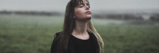 photo of woman standing in field on cloudy day with eyes closed and head turned to sky