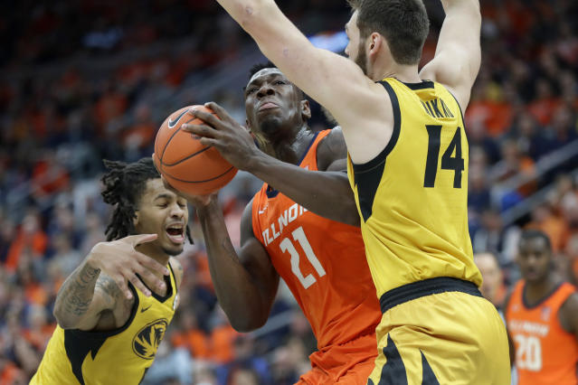 Illinois' Kofi Cockburn (21) heads to the basket as Missouri's Mitchell Smith and Reed Nikko (14) defend during the first half of an NCAA college basketball game Saturday, Dec. 21, 2019, in St. Louis. (AP Photo/Jeff Roberson)