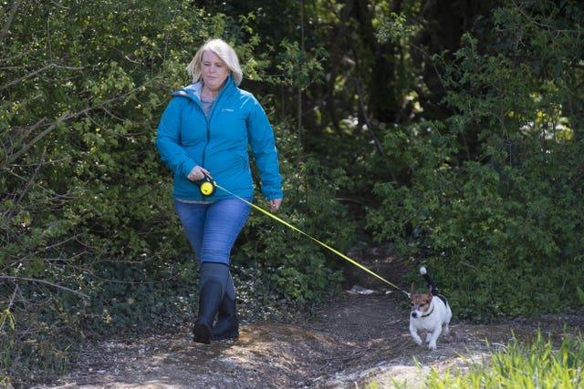 An actress playing the role of PCSO Julia James walks her Jack Russell dog Toby, who was found at the scene, during a reconstruction of the route taken by Julia