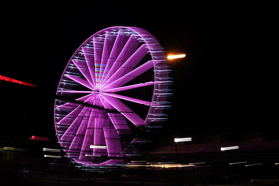 A ferris wheel glows in the evening near downtown in St. Louis on Wednesday, May 19, 2021. (AP Photo/Brynn Anderson)