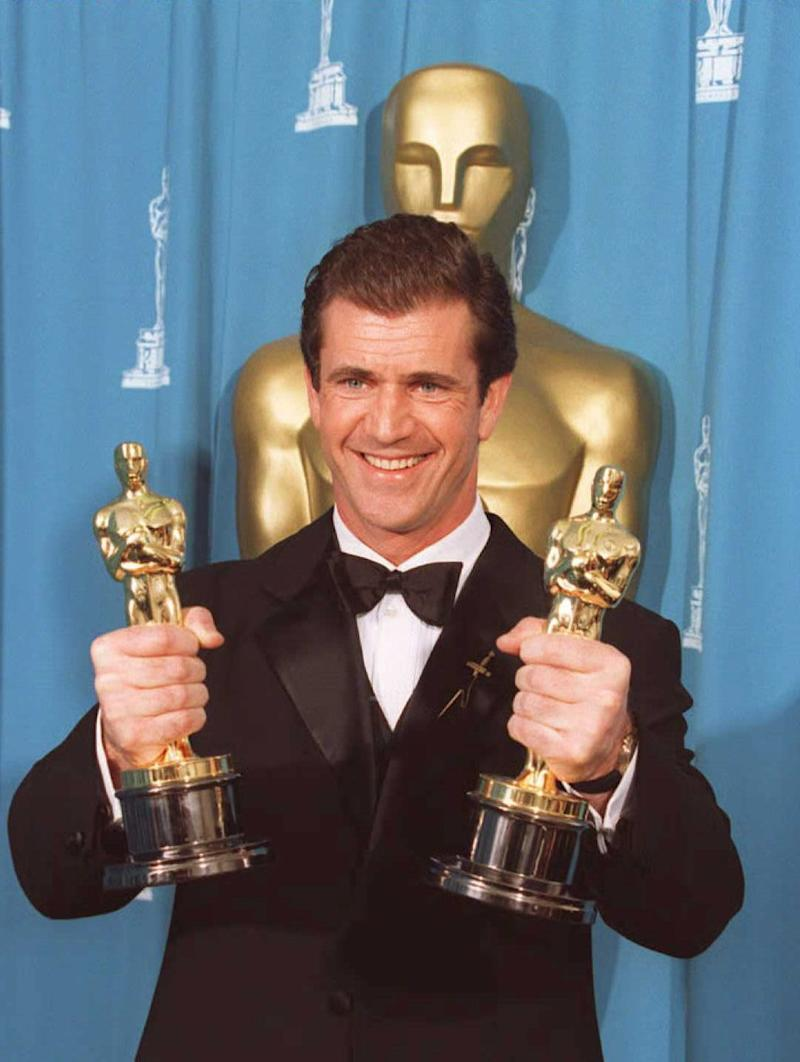 "LOS ANGELES, UNITED STATES: Mel Gibson holds Oscars for Best Director and Best Picture for ""Braveheart,"" at the Dorothy Chandler Pavillion in Los Angeles 25 March 1996 at the 68th annual Academy awards. Gibson shared the Best Picture award with producers Alan Ladd and Bruce Davey. AFP PHOTO Jeff HAYNES (Photo credit should read JEFF HAYNES/AFP via Getty Images)"
