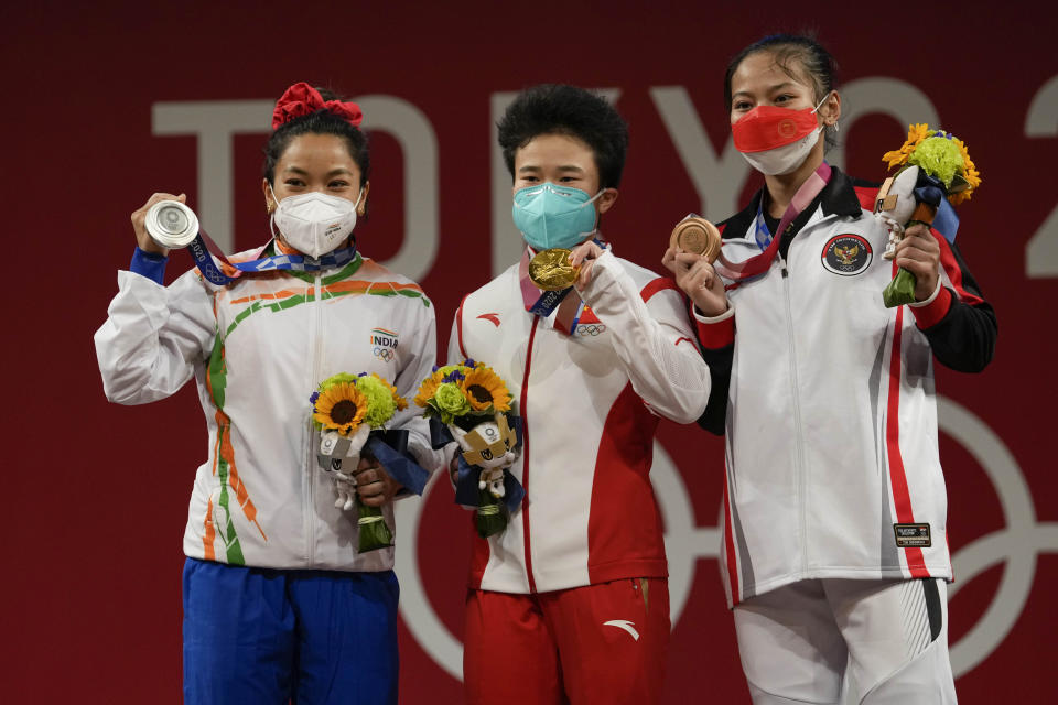 Gold medalist, Hou Zhihui of China, center, stands with silver medalist Mirabai Chanu Saikhom of India, left, and bronze medalist Windy Cantica Aisah of Indonesia, right, after the women's 49kg weightlifting event, at the 2020 Summer Olympics, Saturday, July 24, 2021, in Tokyo, Japan. (AP Photo/Luca Bruno)