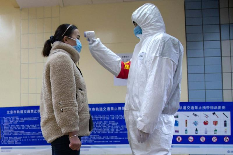 Taking precautions: with fears growing that the coronavirus will spread from China, a health official checks a woman's temperature on the underground in Beijing: Getty Images