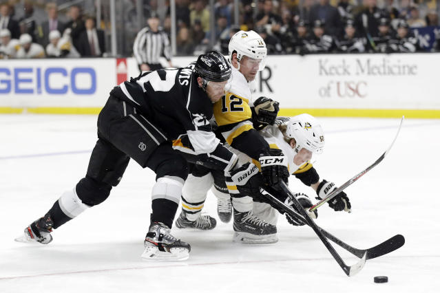 Los Angeles Kings' Trevor Lewis, left, is defended by Pittsburgh Penguins' Patrick Marleau, center, and Juuso Riikola during the second period of an NHL hockey game Wednesday, Feb. 26, 2020, in Los Angeles. (AP Photo/Marcio Jose Sanchez)