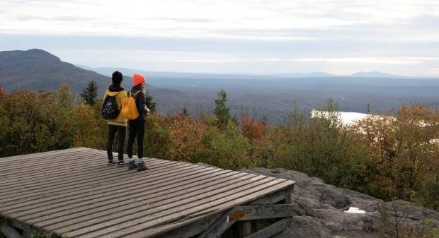 Hikers look out from a camping platform on top of Mont Chauve in Mont-Orford provincial park. (Paul Dussault - image credit)