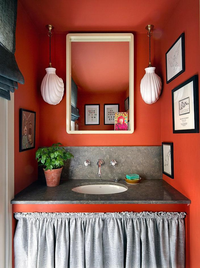 Paint & Paper Library paint in Caravan and polished limestone countertops accent the powder bath.