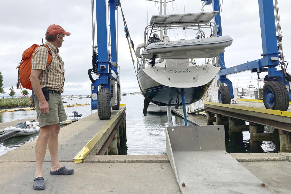 Robin Berthet, of Sheffield, Mass., watches as his sailboat is hauled out of the water onto dry land in advance of an expected storm, Friday Aug. 20, 2021, in Plymouth, Mass. New Englanders, bracing for their first direct hit by a hurricane in 30 years, are taking precautions as Tropical Storm Henri barrels toward the southern New England coast. (AP Photo/Phil Marcelo)
