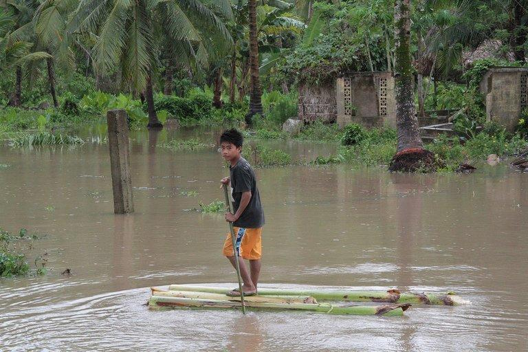 A boy is seen riding on a makeshift raft during flooding in southern Philippines, on December 4, 2012