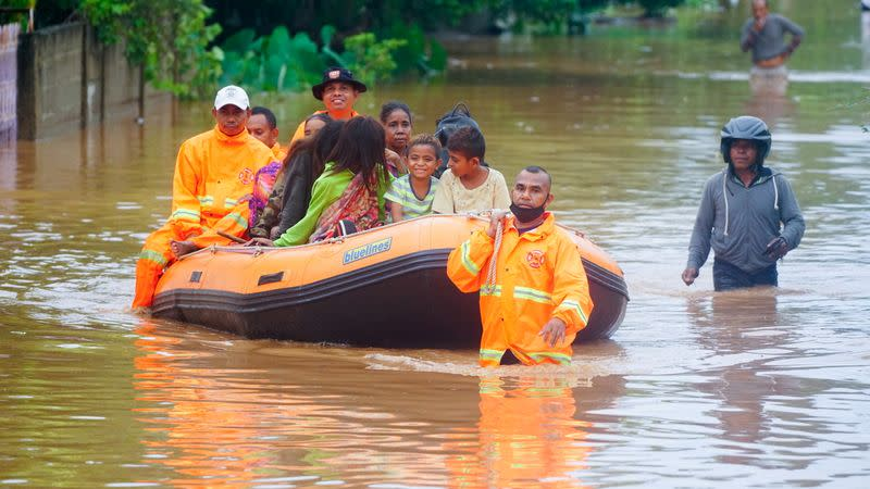 Rescue workers evacuate people through the water in an area affected by floods after heavy rains in Dili