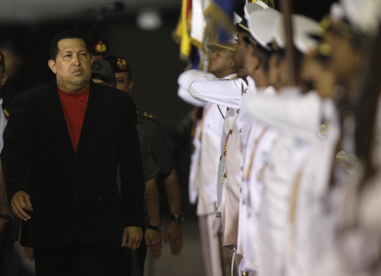 Venezuela's President Hugo Chavez reviews the troops upon his arrival at the Simon Bolivar airport in Maiquetia , Venezuela, Friday March 16, 2012. Chavez returned home Friday nearly three weeks after undergoing cancer surgery in Cuba. (AP Photo/Fernando Llano)